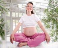 Йога беременной женщины практикуя Стоковые Изображения
