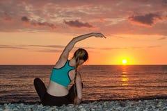 йога девушки пляжа практикуя Взгляд от задней части, заход солнца Стоковые Фото