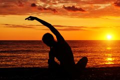 йога девушки пляжа практикуя Взгляд от задней части, заход солнца, силуэты Стоковое Изображение