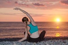 йога девушки пляжа практикуя Взгляд от задней части, заход солнца Стоковое Изображение RF