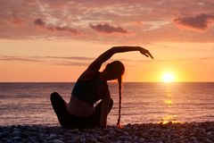 йога девушки пляжа практикуя Взгляд от задней части, заход солнца Стоковая Фотография RF
