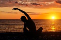 йога девушки пляжа практикуя Взгляд от задней части, заход солнца, s Стоковые Изображения