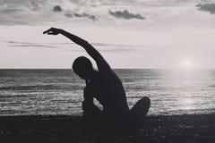 йога девушки пляжа практикуя Взгляд от задней части, силуэты черная белизна Стоковое Изображение