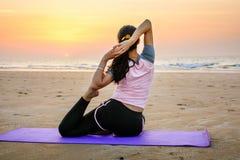Йога девушки практикуя на пляже на заходе солнца Стоковые Изображения RF