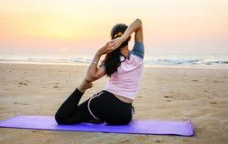 Йога девушки практикуя на пляже на заходе солнца Стоковое фото RF