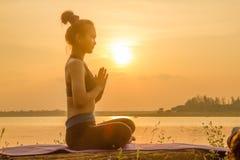 Йога женщины Азии силуэта на заходе солнца Стоковое Изображение RF