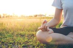 Йога женщины в парке в позиции лотоса ослабляет в природе Стоковая Фотография