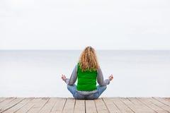 йога женщины заднего океана моста сидя Стоковые Изображения