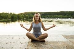 Йога женщины ослабляет в пристани на заходе солнца стоковые фотографии rf