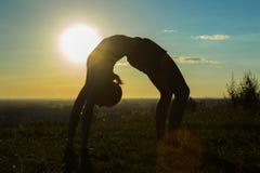 Йога женщины практикуя в парке на заходе солнца - упадите назад, представление колеса Стоковые Фотографии RF