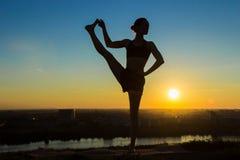 Йога женщины практикуя в парке на заходе солнца Стоковые Фотографии RF