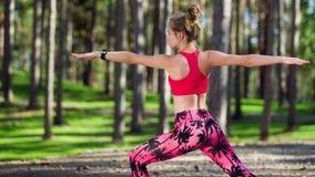 Йога женщины практикуя в представлении ратника леса Штиль, ослабляет, разум и концепция счастья тела Стоковые Изображения