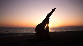 Йога женщины практикуя, заход солнца в пляже Стоковые Изображения RF
