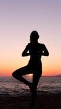 Йога женщины практикуя, заход солнца в пляже Стоковое фото RF