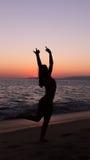 Йога женщины практикуя, заход солнца в пляже Стоковое Изображение RF