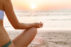 Йога женщины практикуя морем на заходе солнца стоковая фотография