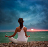 Йога женщины практикуя морем на заходе солнца Стоковая Фотография RF