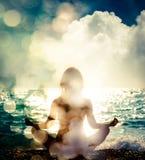 Йога женщины практикуя морем нот bokeh предпосылки замечает тематическое Стоковая Фотография RF