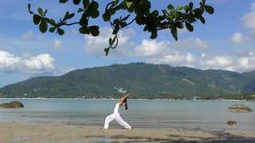 Йога женщины практикуя на море на тропическом острове сток-видео