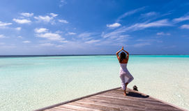 Йога женщины практикуя на моле Стоковые Изображения