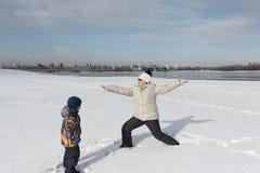 Йога женщины практикуя на речном береге снега весной Стоковые Фото