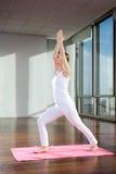 Йога женщины практикуя на циновке стоковые изображения