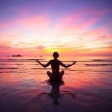 Йога женщины практикуя сидя на пляже Стоковые Изображения