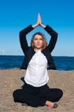 йога женщины представления дела пляжа сидя Стоковое Изображение