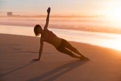 йога женщины пляжа практикуя Стоковые Изображения