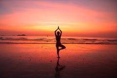Йога женщины силуэта на пляже океана Стоковые Изображения RF