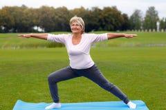 Йога зрелой женщины практикуя в парке стоковые фотографии rf
