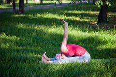 Йога и гимнастика гибкой молодой женщины практикуя в парке Йога в парке, outdoors, здоровье ` s женщин, женщина йоги Стоковая Фотография