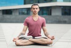 Йога красивого человека практикуя в представлении лотоса outdoors стоковые изображения