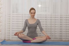 Йога красивой белокурой женщины практикуя протягивая дома на голубой циновке в сером bodysuit и розовых носках Стоковые Изображения RF