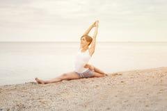 Йога красивой девушки практикуя на пляже около моря Сидит на шпагате, делает протягивать Стоковое фото RF