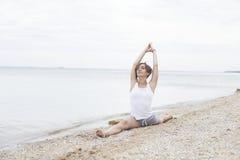 Йога красивой девушки практикуя на пляже около моря Сидит на шпагате, делает протягивать Стоковые Фото