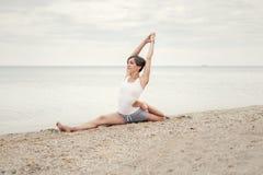 Йога красивой девушки практикуя на пляже около моря Сидит на шпагате, делает протягивать Стоковая Фотография RF