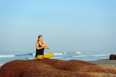 Йога красивой молодой женщины практикуя и тренировки протягивать на п стоковое изображение rf