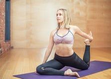 Йога красивой молодой женщины практикуя в студии Стоковые Фото