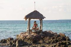 Йога красивой молодой женщины практикуя на пляже на заходе солнца Стоковые Фотографии RF