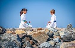Йога мальчика и девушки практикуя на пляже Стоковое Изображение