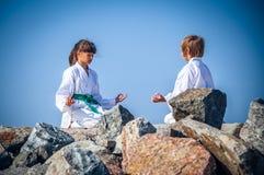Йога мальчика и девушки практикуя на пляже Стоковое фото RF