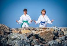 Йога мальчика и девушки практикуя на пляже Стоковые Изображения RF