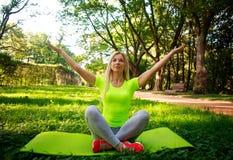 Йога молодой атлетической женщины практикуя работает в парке города Стоковая Фотография RF