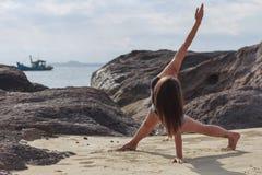 Йога молодой женщины практикуя на пляже Стоковая Фотография