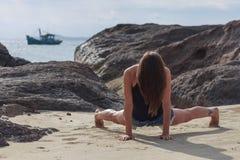 Йога молодой женщины практикуя на пляже Стоковые Изображения