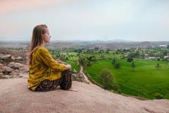 Йога молодой женщины практикуя на скале горы на восходе солнца в Hamp Стоковые Изображения
