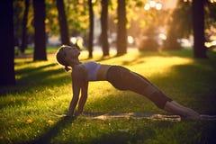 Йога молодой женщины практикуя, протягивая в тренировке Purvottanasana - верхнем представлении планки в парк на заходе солнца Стоковые Фотографии RF