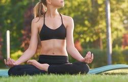 Йога молодой женщины практикуя outdoors на парке Стоковые Фотографии RF