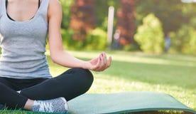 Йога молодой женщины практикуя outdoors на парке Стоковое Фото